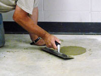 Repairing the cored holes in the concrete slab floor with fresh concrete and cleaning up the Endicott home.