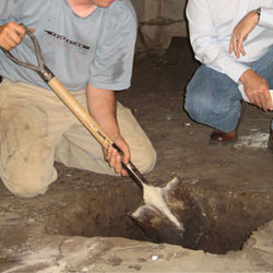 Digging a hole for the engineered fill used in a crawl space support system installation in Rome