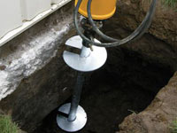 Installing a helical pier system in the earth around a foundation in Ithaca