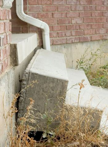 sinking outdoor concrete steps showing cracking and soil washout in Horseheads