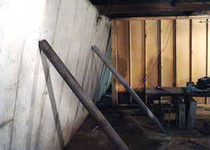 A severely tilting foundation wall propped up by steel beams in Syracuse, Ithaca, Utica, Binghampton.
