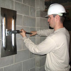installing a wall anchor to repair an bowing foundation wall in Auburn