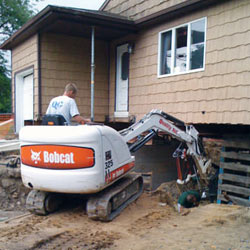 Excavating to expose the foundation walls and footings for a replacement job in Oswego