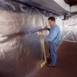 Installation of a radiant heat and vapor barrier on a basement wall in Potsdam